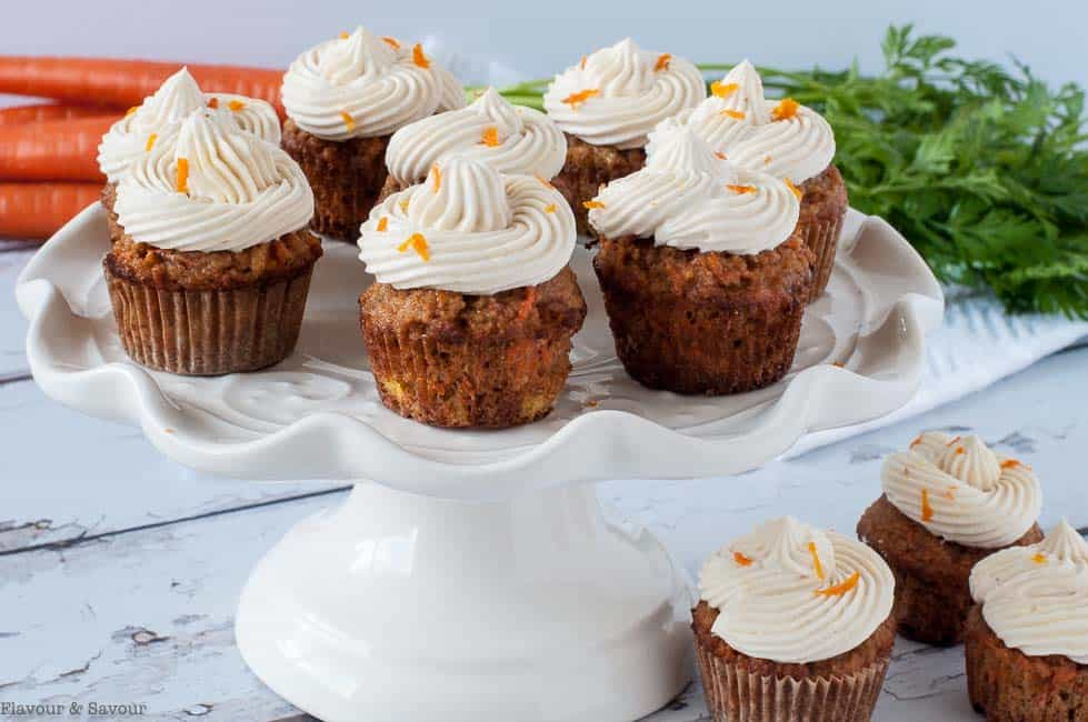 Mini gluten-free carrot cake cupcakes with cream cheese frosting on a pedestal stand.