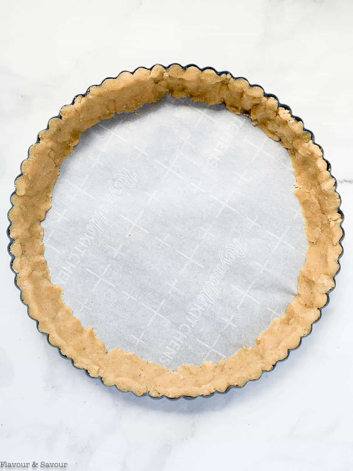 Pressing almond flour crust into edges of pan.