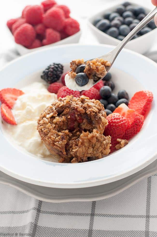 Serving suggestion:: Mixed Berry Baked Oatmeal Cups in a bowl with yogurt or kefir and fresh berries.