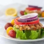 Open Face Harissa Chicken Burger on a wedge of lettuce garnished with red onion and red pepper rings and Greek Yogurt Sauce