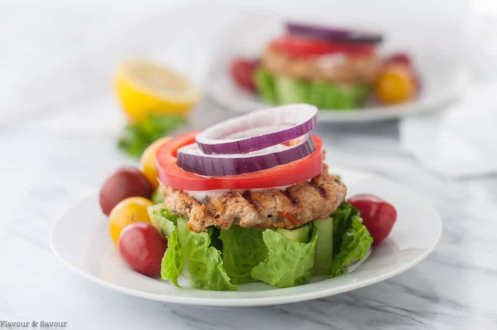 Open Faced Harissa Chicken Burgers on a wedge of lettuce garnished with red onion and red pepper rings and Greek Yogurt Sauce