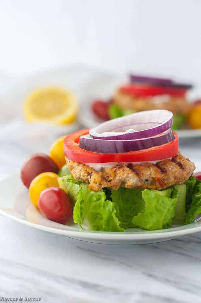 Open-faced Harissa Chicken Burger on a wedge of lettuce garnished with red onion and red pepper rings and Greek Yogurt Sauce
