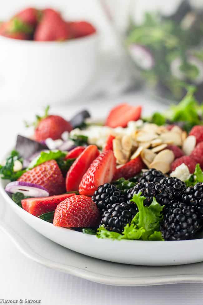 close up view of salad with blackberries, strawberries, raspberries and flaked almonds