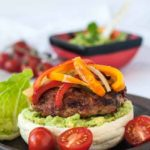 Paleo Chicken Fajita Burgers with Tomatillo Guacamole on a plate with guacamole in the background
