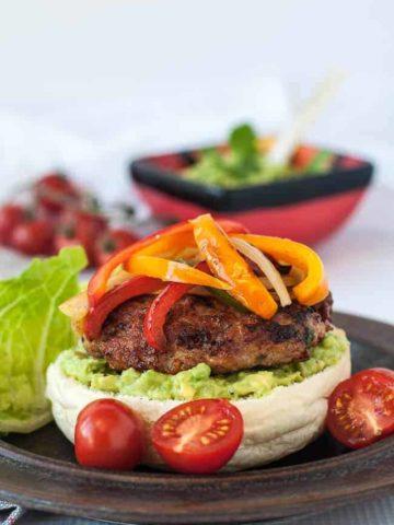 Paleo Chicken Fajita Burgers with Tomatillo Guacamole on a plate with guacamole in the background