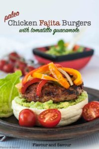 Paleo Chicken Fajita Burger on tomatillo guacamole with sliced peppers and onions on top.