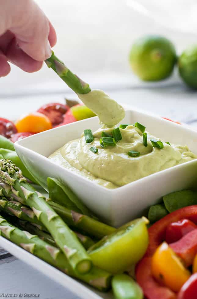 Dipping asparagus spears into Mayo-Free Avocado Green Goddess Dressing and Dip