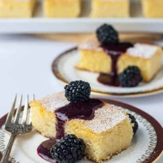 Flourless Lemon Almond Ricotta Cake with Blackberry Coulis on a plate with a fork