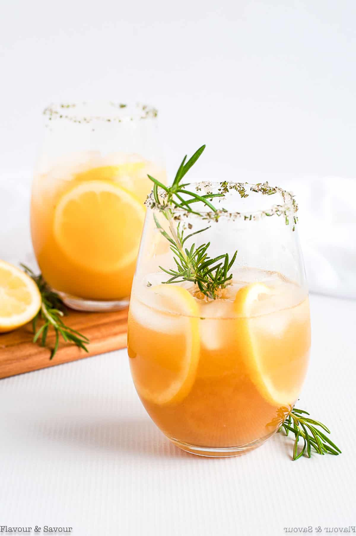 A glass of Pineapple Ginger Kombucha Cocktail garnished with rosemary