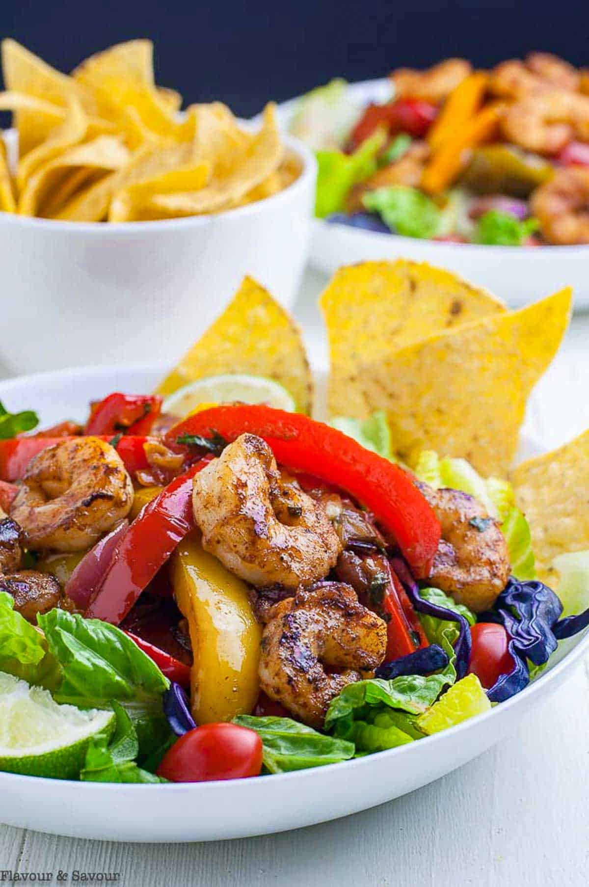 Close up view of Shrimp Fajita Salad with peppers and tortilla chips