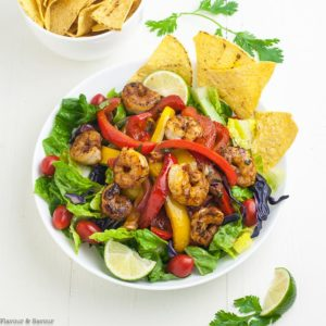 overhead view of Shrimp Fajita Salad in a white bowl with tortilla chips