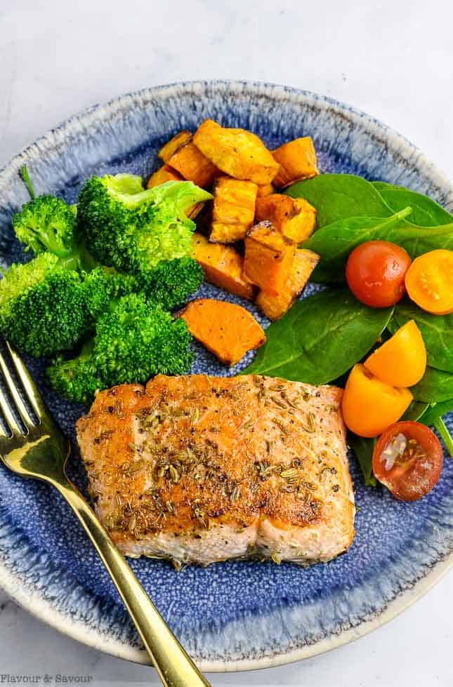 Fennel Crusted Salmon with salad and veggies on a blue plate