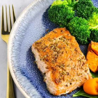 Fennel Crusted Salmon with broccoli on a blue stoneware plate