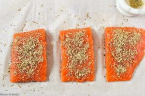 Adding fennel seeds to salmon fillets