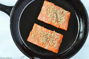 Adding fennel-crusted salmon fillets to a cast iron skillet