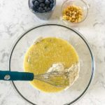 Adding wet ingredients to dry ingredients to make Gluten-Free Blueberry Buttermilk Cornbread Muffins