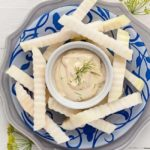 raw kohlrabil sticks on a blue patterned plate with a bowl of Dijon Dilly Dip