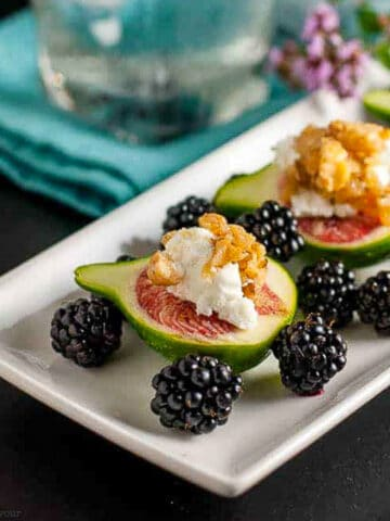 fresh figs with goat cheese and maple walnuts on a platter with blackberries