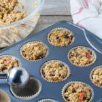 Filling muffin cups with Cranberry-Apple Pumpkin Baked Oatmeal mixture.