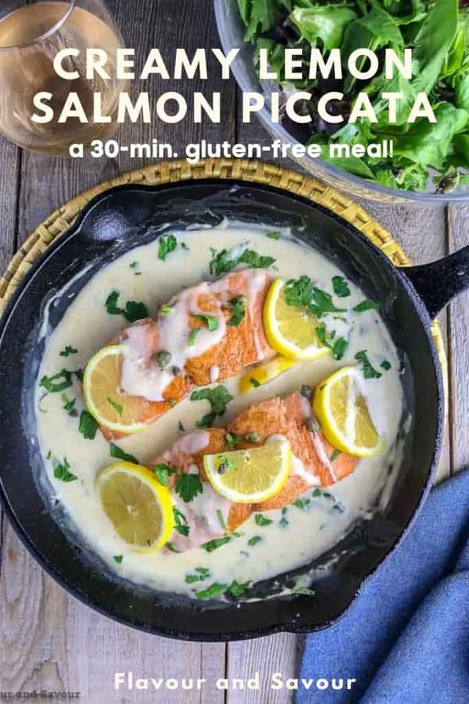 Creamy Lemon Salmon Piccata in a cast iron pan garnished with lemon slices with a salad in the background