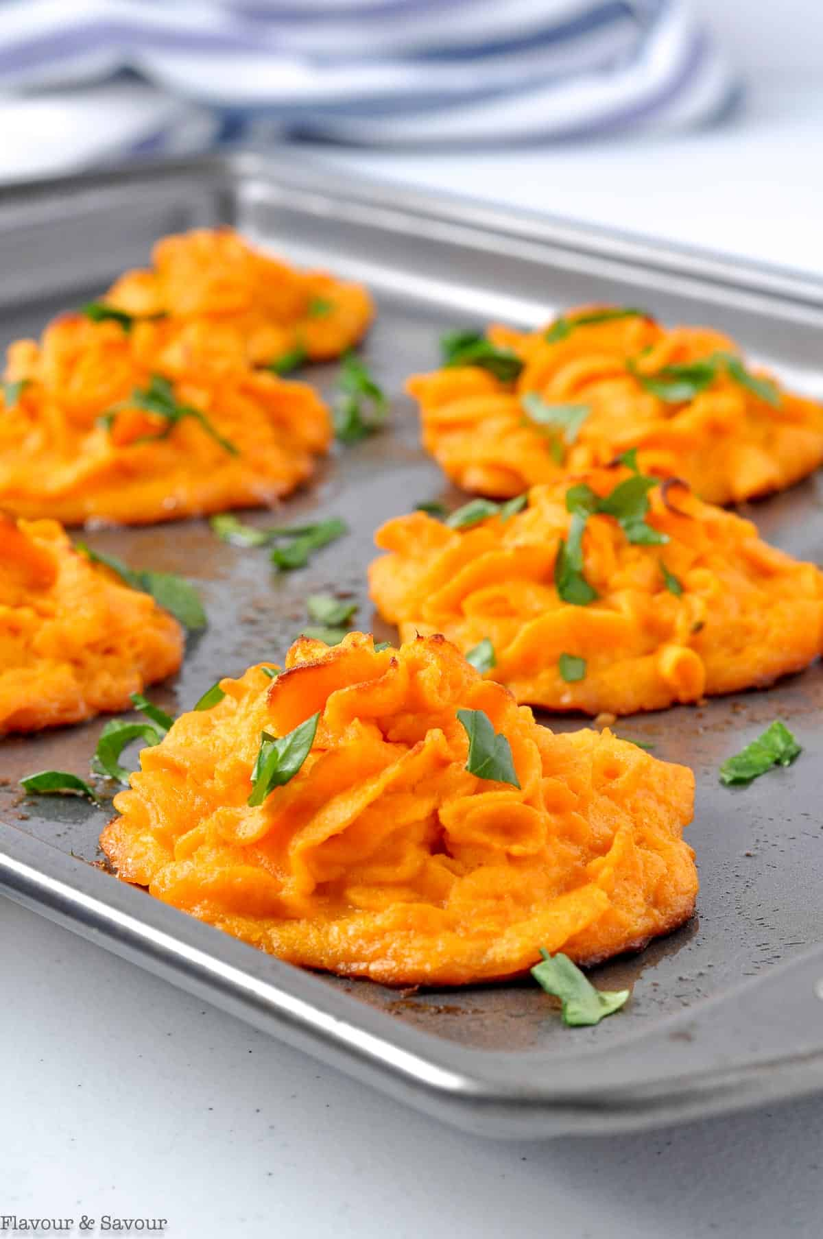 Duchess sweet potato mounds on a baking sheet garnished with parsley