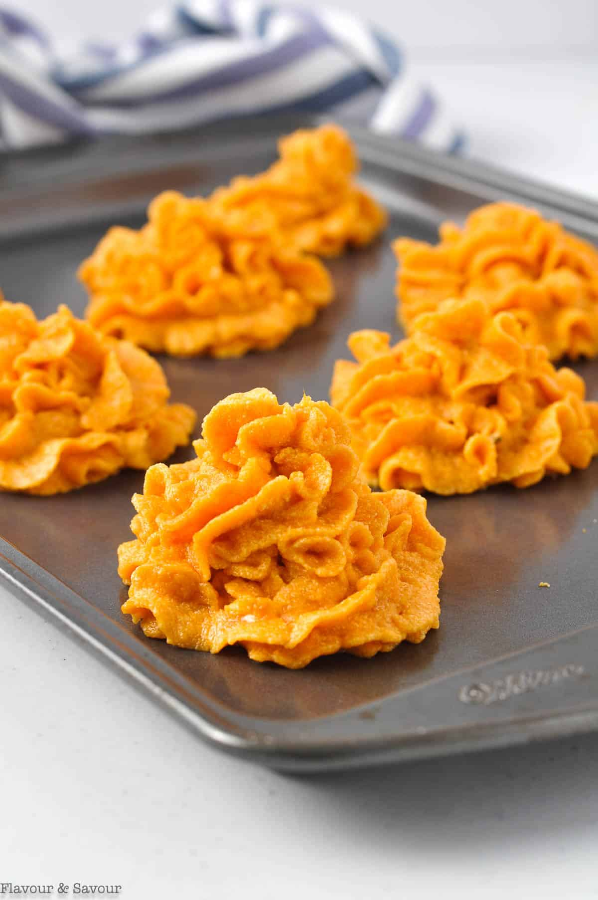 Piped mounds of sweet potatoes on a baking sheet