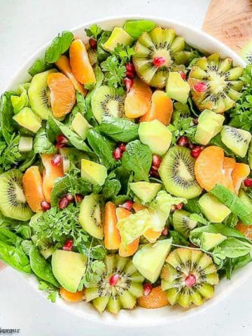 Overhead view of a round white bowl filled with Kiwi Mandarin Spinach Salad with kiwi flowers