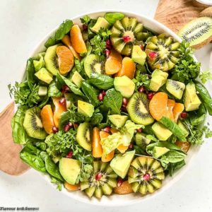 Overhead view of a bowl of Kiwi Mandarin Spinach Salad garnished with kiwi flowers
