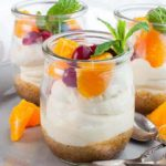 a tiny dessert glass with no-bake cheesecake topped with fresh oranges, cranberries and a mint leaf