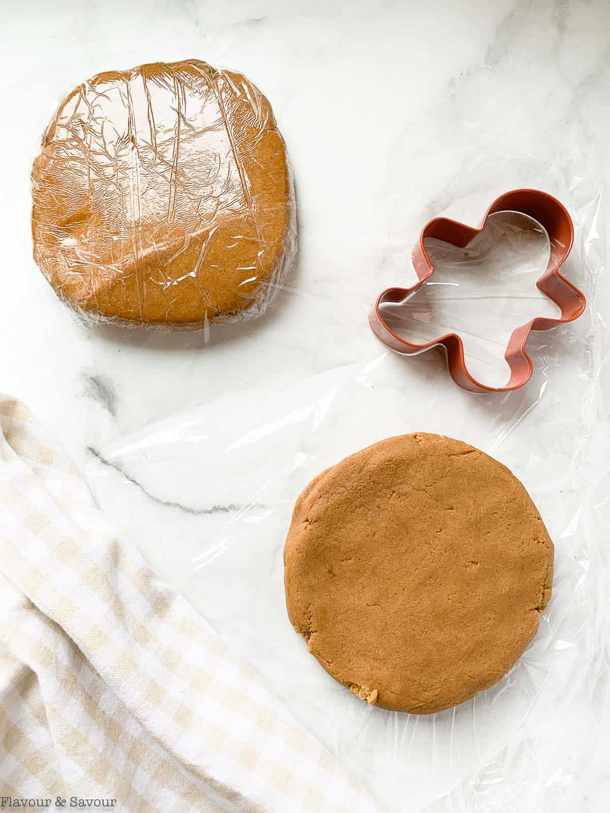 two discs of gingerbread cookie dough wrapped in plastic