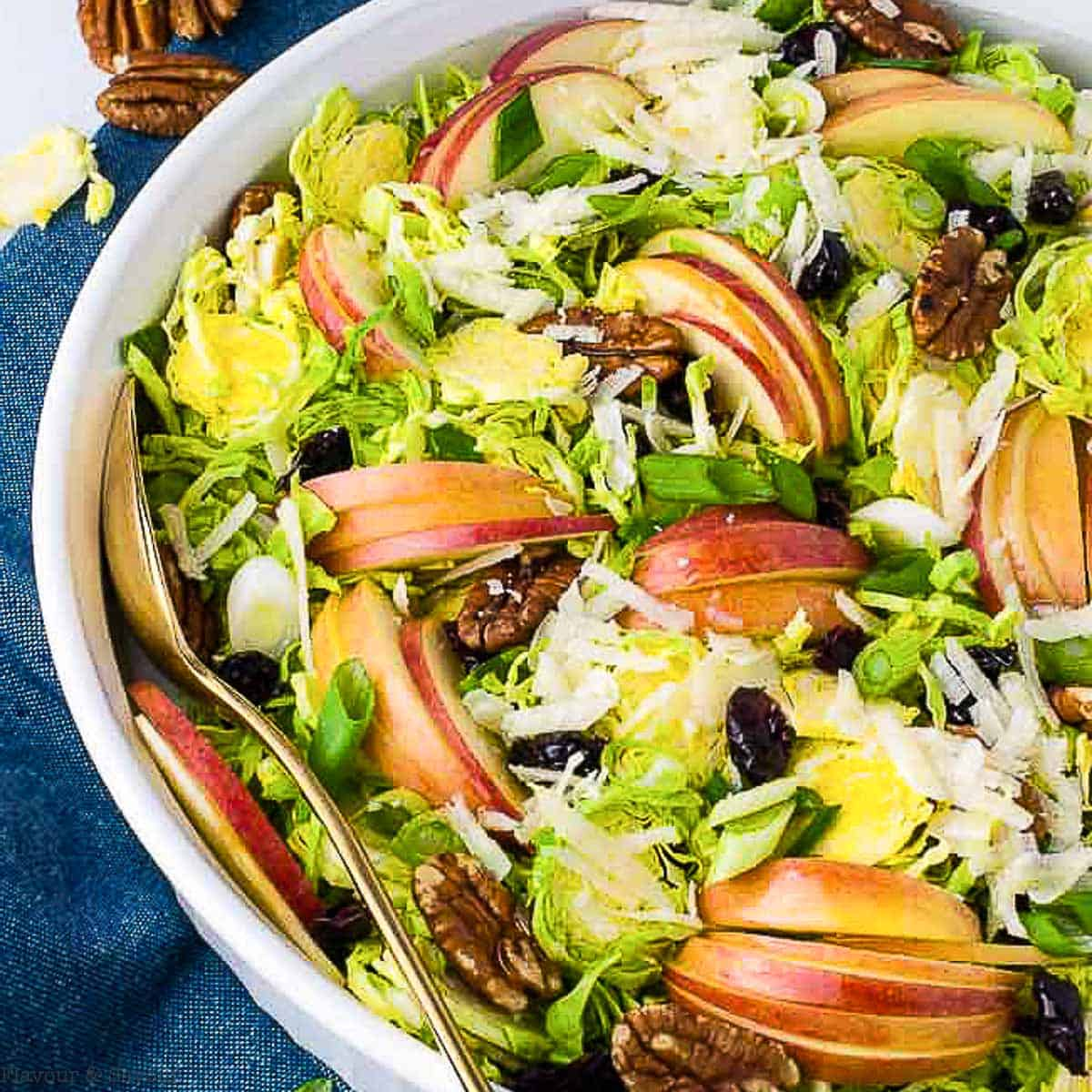 overhead view of a bowl of shaved Brussels Sprout salad with sliced apples and pecans