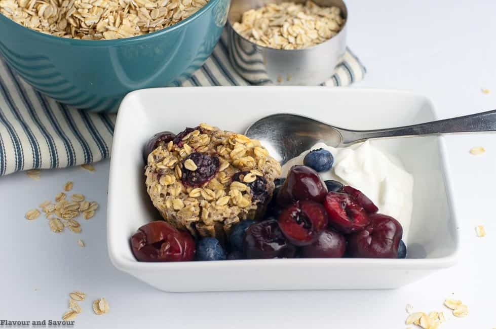 Serving suggestion for Cherry Vanilla Baked Oatmeal Cups with cherries and blueberries