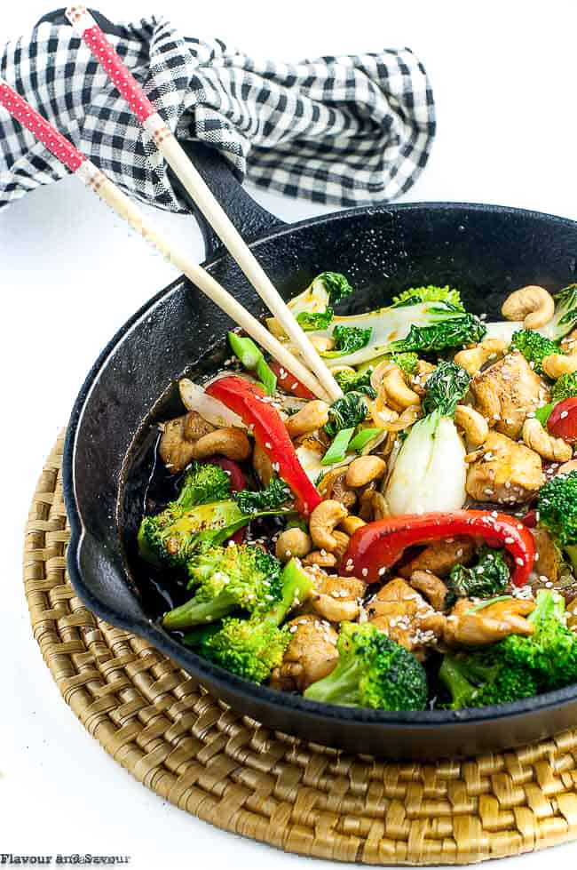 Stir Fry with chicken and broccoli in a cast iron pan with chop sticks