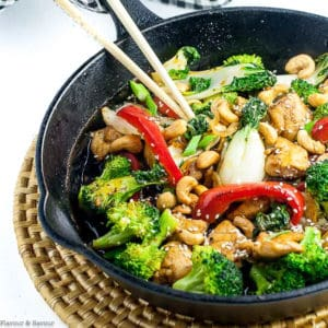 Chicken stir fry in cast iron pan with broccoli and red peppers