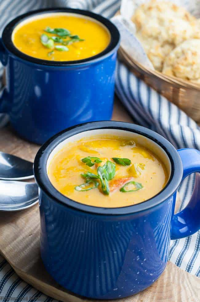 Two blue mugs of Sweet Potato Corn Chowder with baking powder biscuits in the background