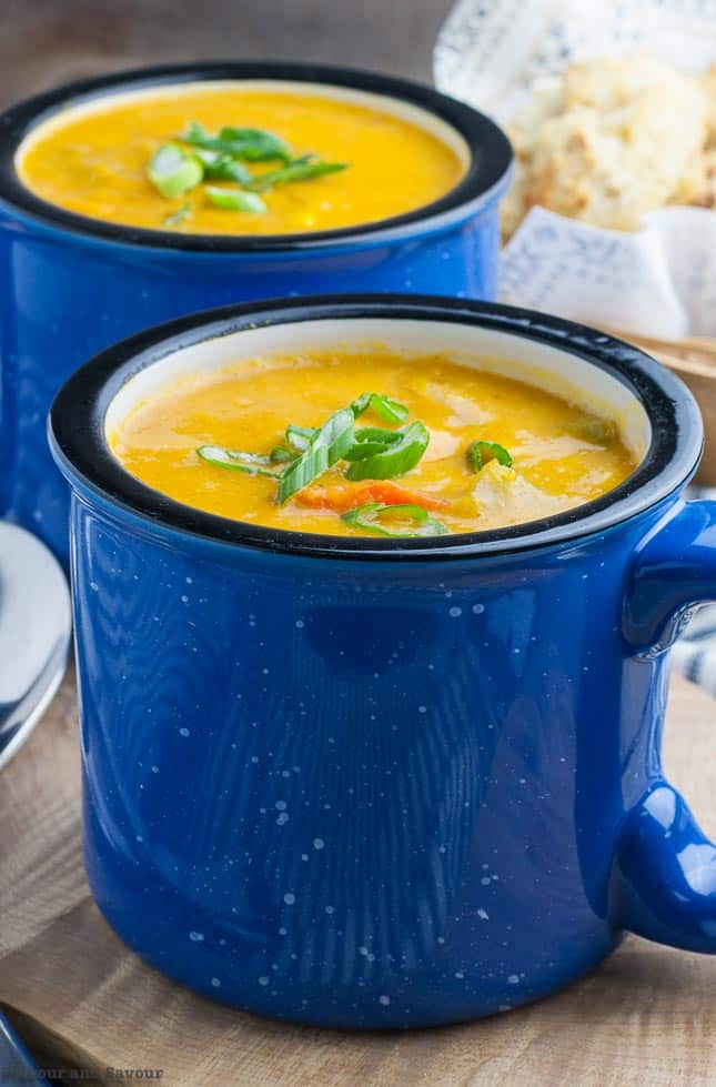 Close up view of Hearty Vegan Sweet Potato Corn Chowder in two blue mugs