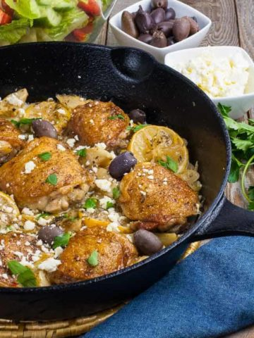 One Pan Baked Lemon Artichoke Chicken Thighs in a cast iron skillet