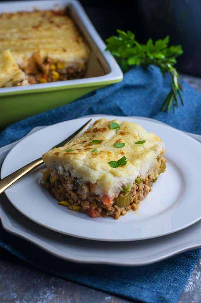 A serving of Shepherd's Pie with Mashed Cauliflower Crust on a plate with the casserole dish in the background