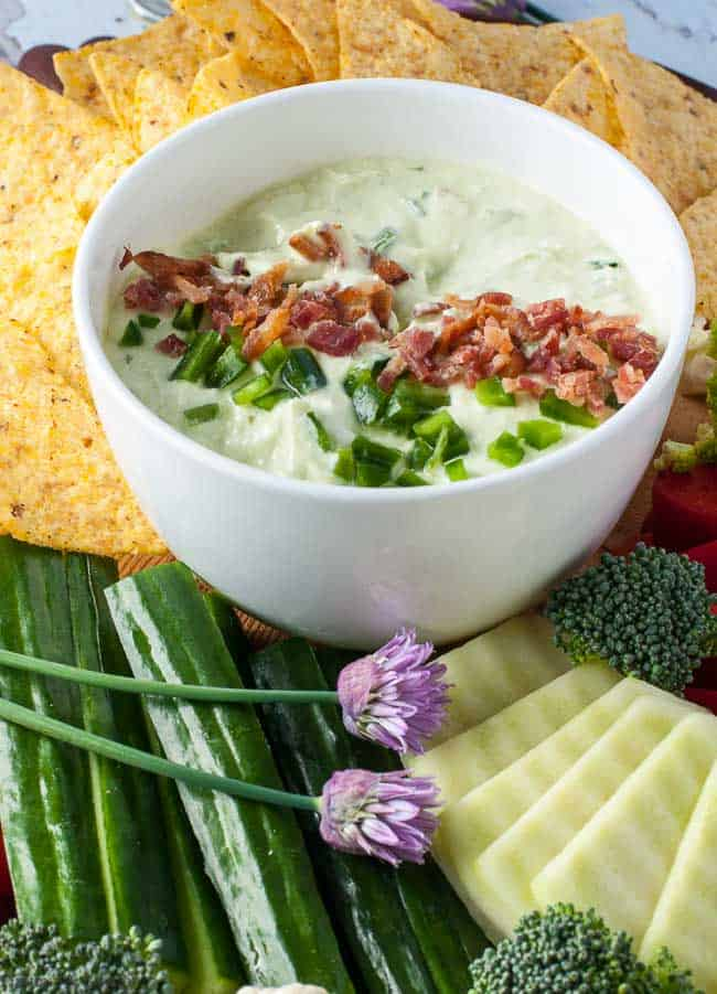 Close up view of jalapeno dip  with bacon and chives surrounded by fresh veggies and tortilla chips