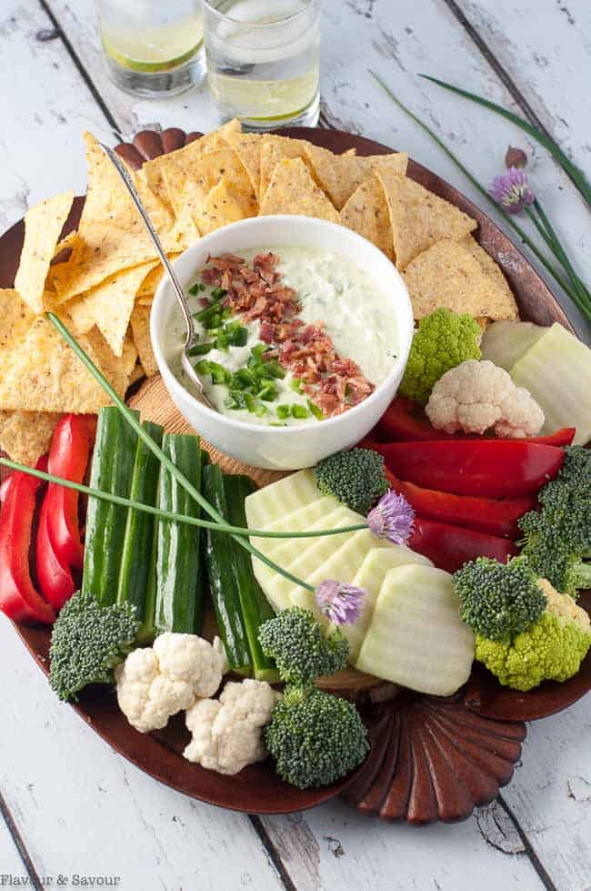 Overhead view of a platter of vegetables and tortilla chips with a bowl of jalapeno dip