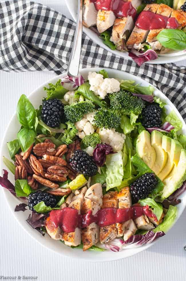 Overhead view of two bowls of Blackberry Balsamic Grilled Chicken Salad with fresh veggies and avocado