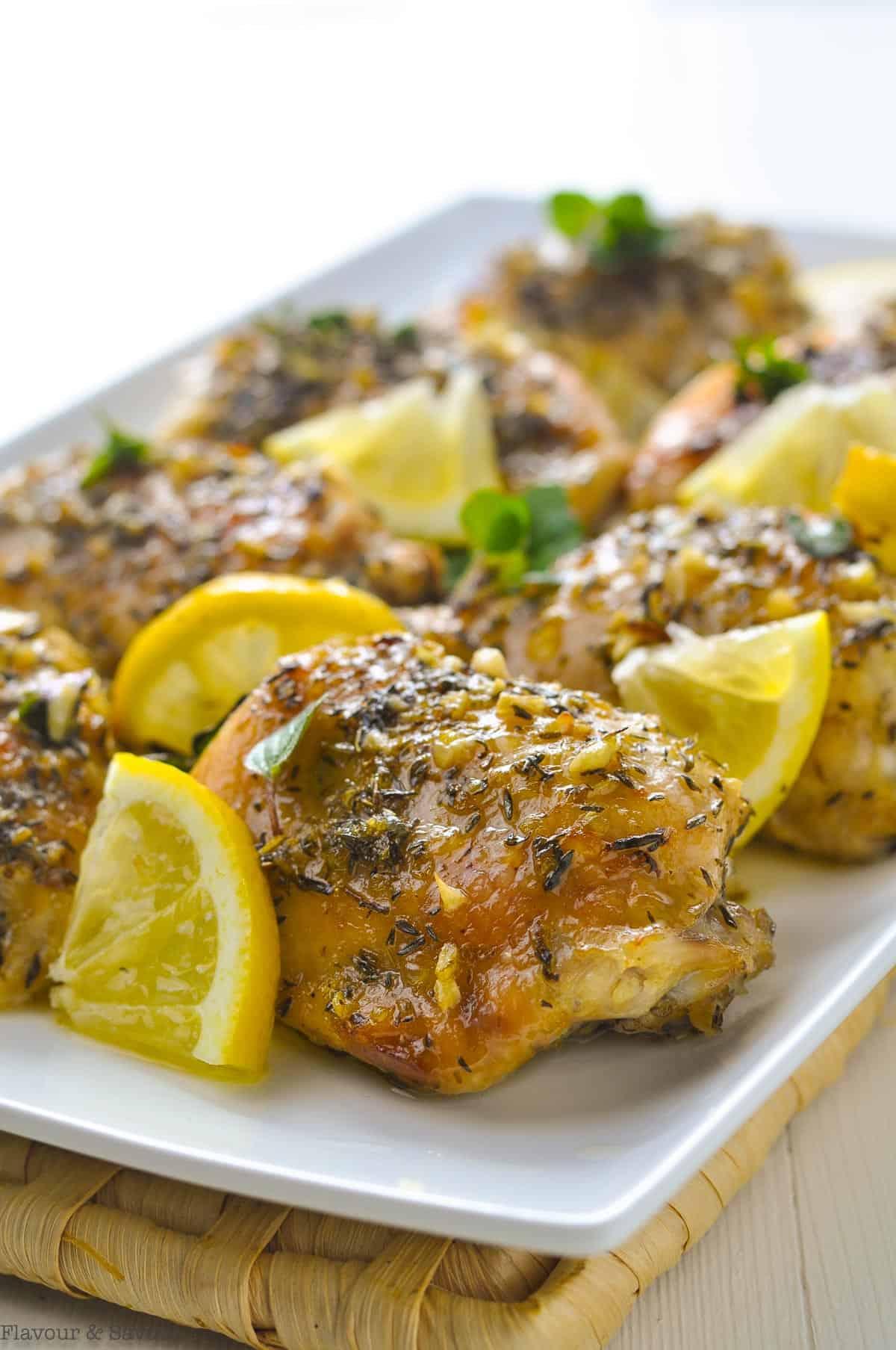 Easy Baked Lemon chicken on a serving platter with lemon slices