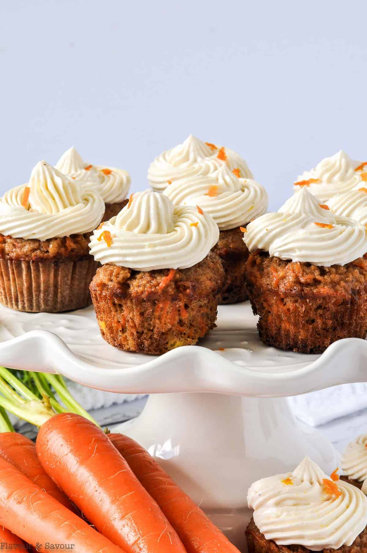 Mini Gluten-Free Carrot Cake Cupcakes on a white pedestal with fresh carrots in the foreground