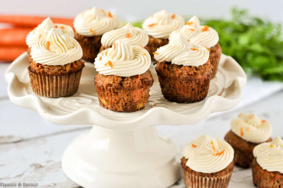 Mini grain-free Carrot Cake Cupcakes on a white pedestal cake plate.