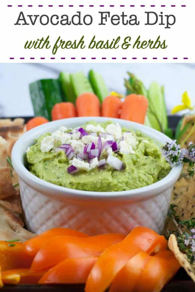 Avocado Feta Dip in a small white bowl surrounded by fresh veggies