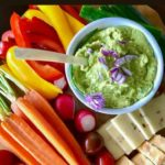 Avocado Feta Dip with fresh basil surrounded by fresh veggies
