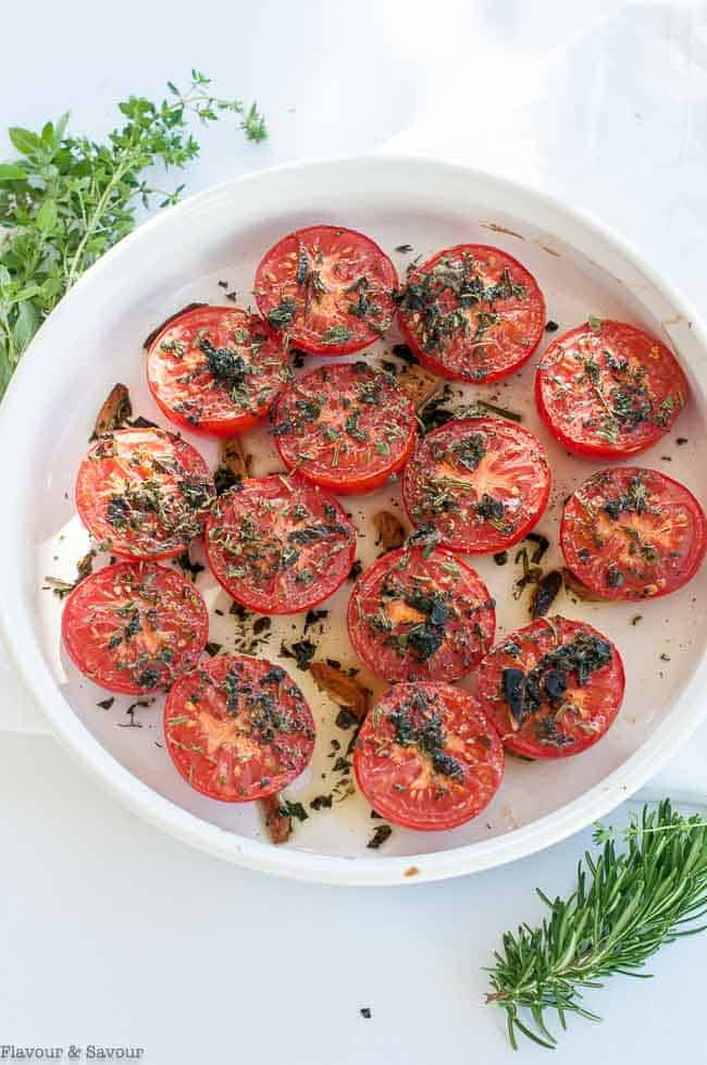Broiled Italian Tomatoes with Garlic and Herbs in a round white dish