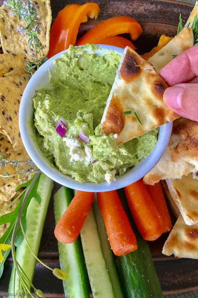 Dipping a pita chip into Avocado Feta Herbed Dip