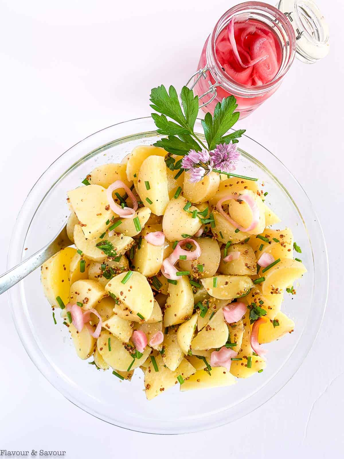 A bowl of Italian potato salad with a jar of pickled shallots beside