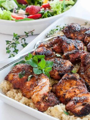 A serving dish full of Cajun chicken thighs on quinoa
